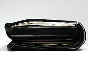 A single fold wallet filled with receipts, cas...
