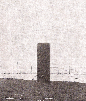 Colorado Springs Notes, 1899–1900 - A coil outside laboratory with the lower end connected to the ground and the upper end free. The lamp is lighted by the current induced in the three turns of wire wound around the lower end of the coil.