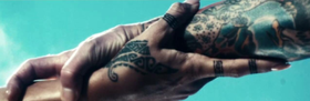 A screenshot of two tattooed hands intertwining