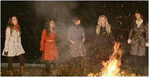 "Issues (The Saturdays song) - One frame of the video for ""Issues"" where The Saturdays standing around a blazing fire."