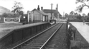 Small wooden railway station with a single rail track. The platform is considerably taller at one end than at the other. Aside from a small wooden building on the platform, the only other visible building is a single farmhouse.