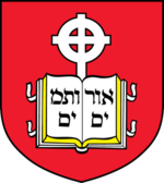 Coat of arms of the school, containing a book device inscribed with Hebrew letters and cross in front of a red background
