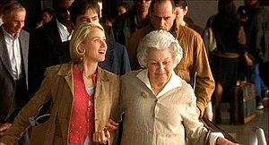 Naomi Watts raggiante e di fronte in luce morbida tenendo il braccio di una donna più anziana, mentre prendono uno scala mobile all'aeroporto internazionale di Los Angeles