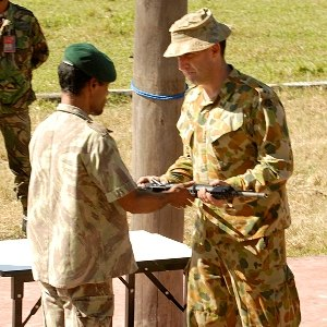2006 East Timorese crisis - Rebel soldier Major Tara (left) hands over his weapon to Lieutenant Colonel Mick Mumford, at a ceremony in the city of Gleno on 5 July.