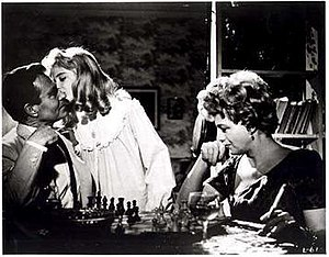 "Lolita (1962 film) - In this scene from the film, Humbert plays chess with Lolita's mother as Lolita kisses Humbert goodnight. His line in the scene is ""I take your Queen"" suggestive of his designs on her daughter. Chess is a recurring motif in the novels of Nabokov and a favorite pastime of director Stanley Kubrick."