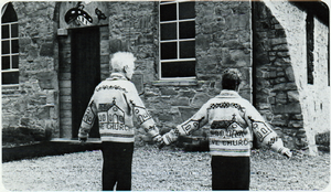 Cowichan knitting - A couple display their themed Cowichan sweaters outside the Butter Church at Cowichan Bay, 1985.