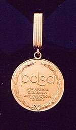"Gold medal encircled in a laurel wreath and inscribed ""PDSA For animal gallantry and devotion to duty"" held from a ring suspended by a golden ribbon."