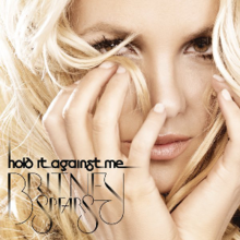 "The face of a blond woman. She has her hands on her cheeks and her wavy hair seems to be in motion, next to her eyes. On the lower left corner, the words ""hold it against me"" are written in black small letters. Below them, the words ""BRITNEY SPEARS"" are written in black capital letters."