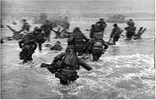A blurry picture of American men moving through the water to the beach.