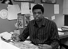 McDuffie seated at a drawing table