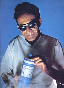 A picture of a blind man wearing dark glasses and a white lab coat grinning while holding a bottle of soap while lit from below. Steam, presumably dry ice, billows from below, giving the photograph a science-fiction feel.