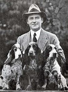 """A greyscale photo of man in a fedora hat and suit with tie standing behind three cocker spaniel with light and dark patches."""