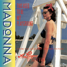 Madonna wearing sunglasses and beachwear, while standing in front of a white lifeguard tower.