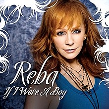 "A woman is standing in front of a wall. She is wearing a blue blouse and four necklaces with crosses at the end. Her hair is red and she has blue eyes. The words ""Reba"" and ""If I Were A Boy"" are written in white capital letters upon her image."