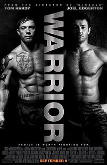 Two shirtless, muscled men stand against a black background. The word