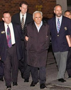 A white-haired man in a black overcoat and dress shirt with his hands behind his back at the center of a small group of men walking toward the camera. The two men on either side are wearing jackets with gold badges clipped to the lapels and ties. They are holding the arms of the man in the center. A fourth man, also in a jacket and tie, is visible in the rear.