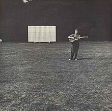 The album cover is a black-and-white photograph of a sports field with a score board in the distance, off-center to the left. Off-center to the right and also in the distance Fred Frith is standing playing a guitar. There is no text on the cover.