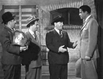 Robert Kellard - Robert Kellard (far right) fires The Three Stooges from their job in 1946's Rhythm and Weep