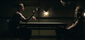 Russian Roulette (song) - A screenshot from the video where Rihanna is seen sitting across her love interest (Jesse Williams) who is holding a revolver.