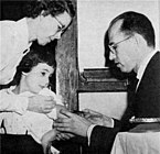 Jonas Salk administering the polio vaccine to a child