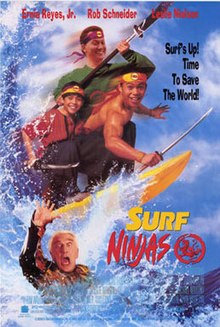 "Three teenage boys stand on a yellow surfboard, riding a tidal wave. They wear yellow-and-orange bandannas, are armed with sword-like weapons, and are smiling. Beneath their surfboard is an old, armored man with a shocked look on his face, reaching up with his right hand for help. Beside the surfboard are the words ""Surf Ninjas"", followed by a dragon emblem."