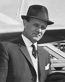 William Harper at an airport, wearing a hat