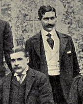 Sullivan, seated, with Herbert standing behind his left shoulder; both are very well-dressed and mustachioed