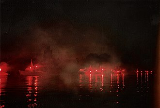 Western Goals Institute - Torchlit small boat flotilla enters the lake at Moln, near Hamburg, as part of the anti-Communist demonstration on 12 August 1989, to which the WGI sent a delegation. Each boat carries a flag of a province or city lost after 1945.