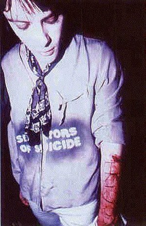 "Richey Edwards - Edwards with 4 Real carved into his arm. The NME discussion as to whether to publish this image was a bonus track on ""Suicide Is Painless""."