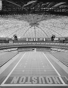 "The interior of a football stadium. The stadium is empty and covered by a large, dome-like roof; the ends of the playing field have large letters spelling ""Houston""."