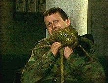 A man in camouflage fatigues winces with pain as he tries to remove a green alien creature from his neck.