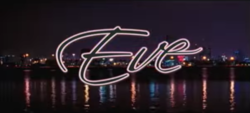 The word Eve is written in black cursive font and is presented against a nighttime panoramic image of downtown Miami.