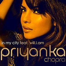 "A photograph showing the face of a young, Indian woman from the left profile against a black background. At the foot of the image are the words ""In My City feat. will.i.am "" and ""Priyanka""."