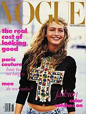 "November 1988 cover of American Vogue magazine, showing model Michaela Bercu, shot from just below the waist in natural outdoor light, wearing a $10,000 jewel-encrusted Christian LaCroix T-shirt with faded 450 jeans. The top headline on the cover reads ""The real cost of looking good"""