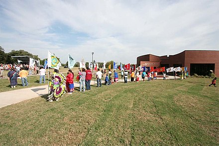 Native American young people hold flags of their tribes at the dedication of the Standing Bear Museum. Ponca City Standing Bear Museum Dedication.jpg