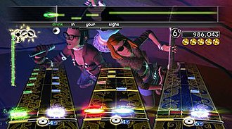 "Rock Band 2 - A screenshot of a full band playing Lush's ""De-Luxe"" in Rock Band 2. Each instrument is represented by a different interface: lead guitar (left), drums (middle), bass guitar (right), vocals (top). The Band Meter (green meter on left) measures the performance of each band member, while the Energy Meter (gold meter beneath each interface) tracks each player's Overdrive."
