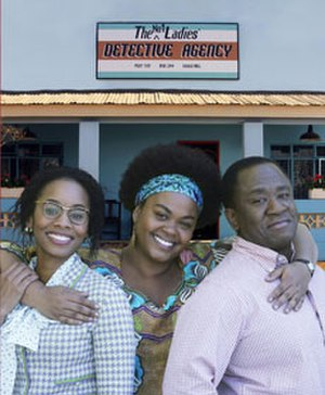 The No. 1 Ladies' Detective Agency (TV series) - Anika Noni Rose as Mma Makutsi, Jill Scott as Mma Ramotswe, and Lucian Msamati as Mr. JLB Matekoni