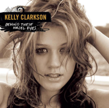 "A black and white frontal image of a woman holding her curly hair at the back of her head. She is looking in front. On her upper left, the word ""Kelly Clarkson"" and ""Behind These Hazel Eyes"" are written in yellow and white capital letters respectively."