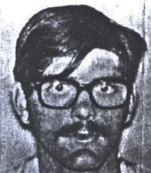 A grainy black-and-white photo of a young white man with straight though slightly unkempt hair, a mustache, and bespectacled eyes which stare straight ahead at the camera