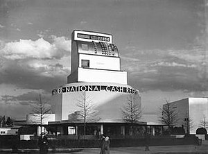 Teague (company) - Designed for the 1939 New York World's Fair, the National Cash Register Building functioned not only as an exhibit center, but as the world's largest active cash register. The design showcases NCR's new 100 Model through the seven-story register atop the building.