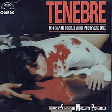 "A figure with dark hair and wearing a white shirt prone in a pool of blood. Above, ""TENEBRE""."