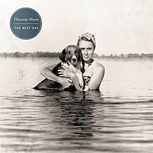 "A black-and-white photograph of a woman in water holding a dog. In the upper-left corner, white text inside a teal circle reads ""Thurston Moore"" in standard case, followed by ""The Best Day"" in uppercase text."