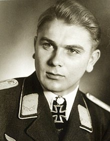 The head and shoulders of a young man, shown in semi-profile. He wears a military uniform with an Iron Cross displayed at the front of his white shirt collar. His hair is blond, short and combed to his back, his nose is long and straight, and his facial expression is emotionless; looking to the right of the camera.