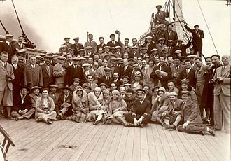 New York Philharmonic - Arturo Toscanini (standing in the center, sporting a bow tie and cap) with the orchestra aboard the S.S de Grasse, embarking on their European tour, 1930. New York Philharmonic Archives