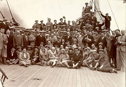 Arturo Toscanini (standing in the center, sporting a bow tie and cap) with the orchestra aboard the S.S de Grasse, embarking on their European tour, 1930. New York Philharmonic Archives