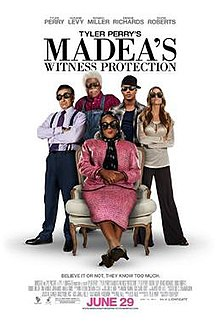 The poster shows five people, four standing and one sitting in chair wearing black sunglasses in a white background. Text at the top of the poster reveals the title. Text at the bottom of the poster reveals the production credits, rating and release date.
