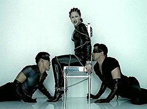 "Human Nature (Madonna song) - Madonna in the bondage inspired video for ""Human Nature"", showing the singer and her dancers in the latex and leather clothing, while being tied to the chair."