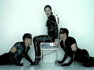 """Human Nature (Madonna song) - Madonna in the bondage inspired video for """"Human Nature"""", showing the singer and her dancers in the latex and leather clothing, while being tied to the chair."""