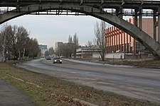 Marshall Malinovsky Street on the left bank of the Dnieper looking west. The arch is part of the railway Merefa-Kherson bridge, which crosses Monastyrsky Island.