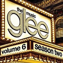 """Prim-plan al unui cort de teatru tradițional cu mai multe etaje, cu lumini de urmărire.  Cuvântul """"Glee"""" este scris în lumină, cu cuvintele """"The Music"""" tipărite mai sus.  totul în minuscule.  Cuvintele """"Volumul 6"""" și """"Sezonul doi"""" sunt tipărite cu litere negre minuscule pe antetul marcii."""